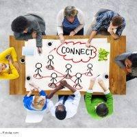"""Acht Personen am Tisch mit """"Connect""""-Papier"""