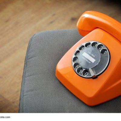 Oranges Telefon auf Stuhl
