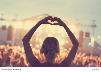 Frau zeigt Herz auf Festival